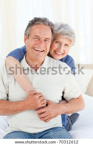 Senior couple hugging on their bed at home - stock photo