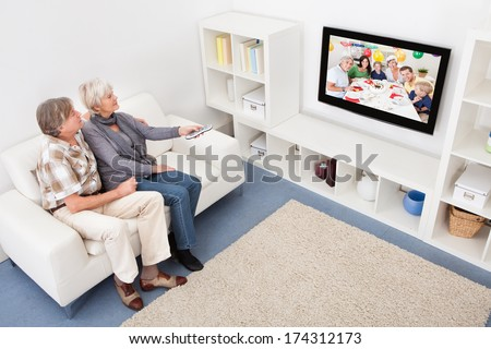 Senior Couple In Living Room Using Remote Control In Front Of Television - stock photo