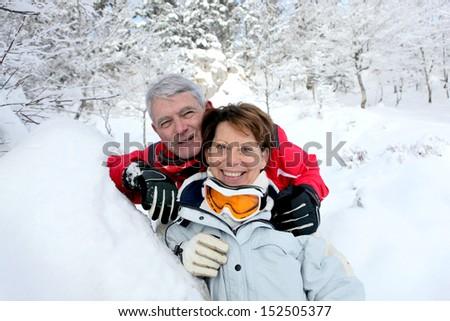 Senior couple in snowy landscape - stock photo