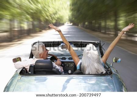 Senior couple in sports car - stock photo