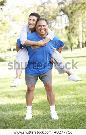 Senior Couple In Sports Clothing Having Fun In Park - stock photo