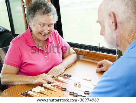 Senior couple in the kitchen of their motor home playing backgammon. - stock photo