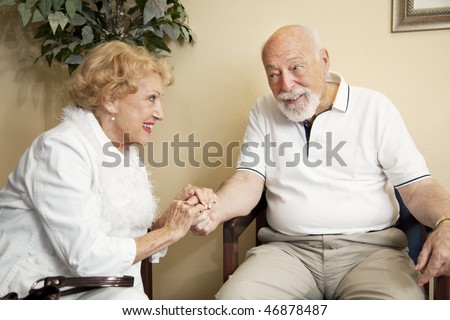 Senior couple in the waiting room of the doctor's office holding hands for moral support. - stock photo