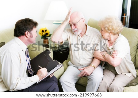 Senior couple in therapy.  Husband is feeling guilty. - stock photo