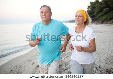 Senior couple jogging on the coast - stock photo