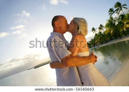 Senior couple kissing at the beach - stock photo
