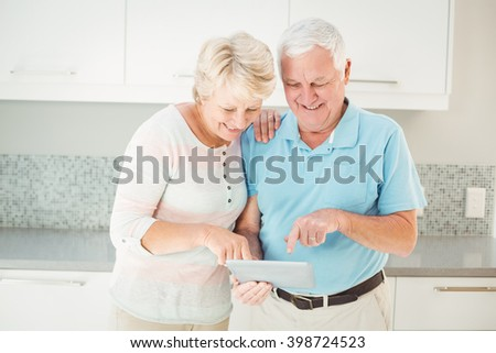 Senior couple laughing using tablet while standing in kitchen - stock photo