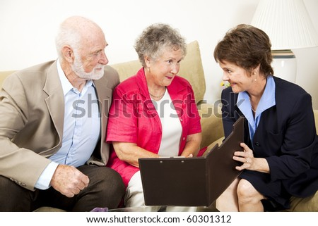 Senior couple listens to a sales pitch in their home. - stock photo