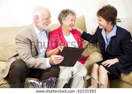 Senior couple listens to a saleswoman or financial consultant in their home. - stock photo