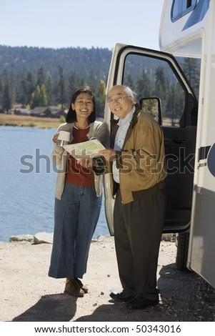 Senior couple looking at map outside RV at lake - stock photo