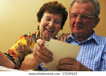 Senior couple looking at old photographs. Reminisce about the past - stock photo