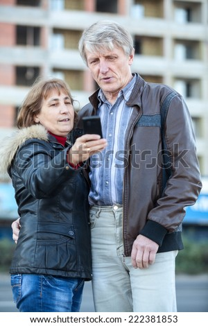Senior couple looking at phone screen after making selfie - stock photo