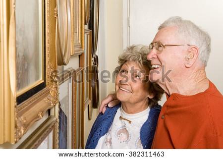 Senior couple looking at photographs - stock photo