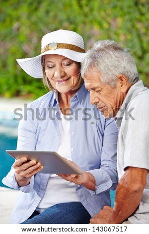 Senior couple looking at tablet computer outdoors at pool - stock photo