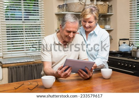 Senior couple looking at tablet pc together at home in the kitchen - stock photo