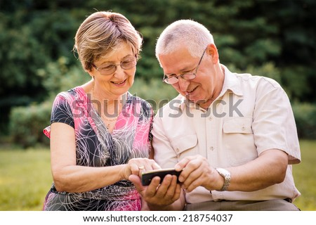 Senior couple looking together on photos in smartphone - outdoor in nature - stock photo