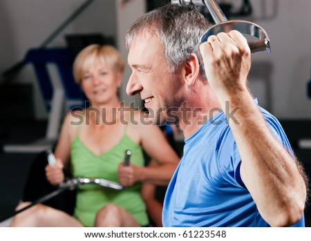 Senior couple -  man and woman - in the gym lifting weights on a lat pull machine, exercising - stock photo