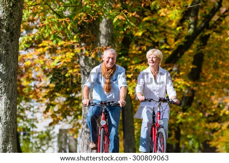Senior couple, man and woman, on bicycles having bike tour in autumn park - stock photo