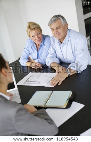 Senior couple meeting architect for building project - stock photo