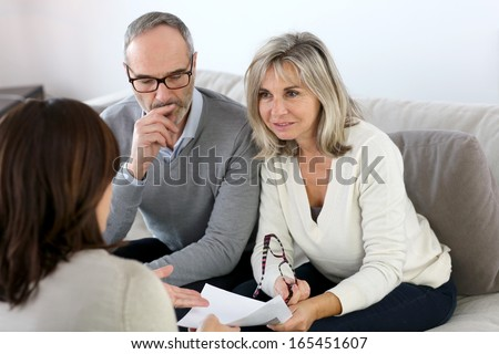 Senior couple meeting financial adviser for investment - stock photo