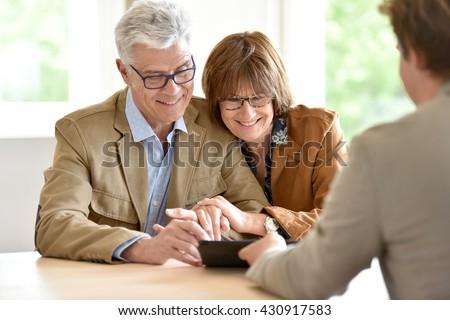 Senior couple meeting financial adviser for investment - stock photo