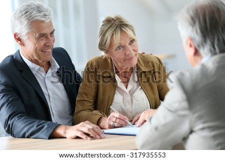 Senior couple meeting real-estate agent for investment - stock photo