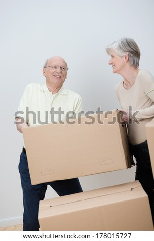 Senior couple moving house stacking brown cardboard cartons filled with their personal belongings as they pack everything up - stock photo