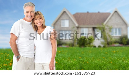 Senior couple near new home. Real estate background. - stock photo