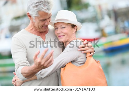 Senior couple of tourists taking picture with smartphone - stock photo