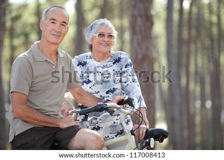 Senior couple on a bicycle - stock photo