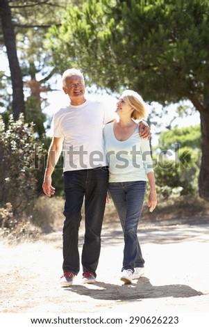 Senior Couple On Romantic Walk In Countryside - stock photo