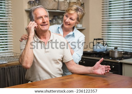 Senior couple on the phone together at home in the kitchen - stock photo