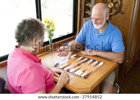 Senior couple on vacation playing backgammon in their motor home.  Motion blur on the man's hand as he shakes the dice. - stock photo
