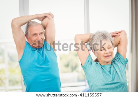 Senior couple performing exercise at home - stock photo