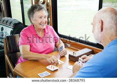 Senior couple playing a cribbage card game in their motor home. - stock photo