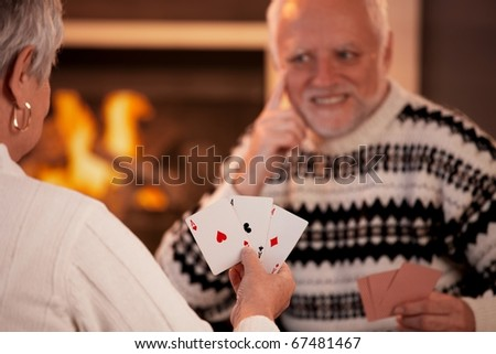 Senior couple playing cards on winter night, cards handheld in focus. - stock photo
