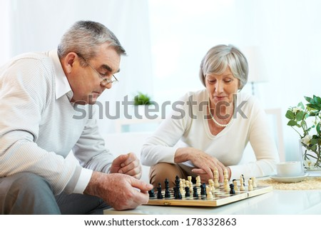 Senior couple playing chess - stock photo