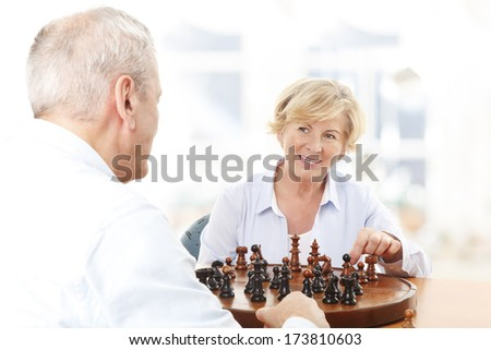 Senior couple playing chess together at home - stock photo