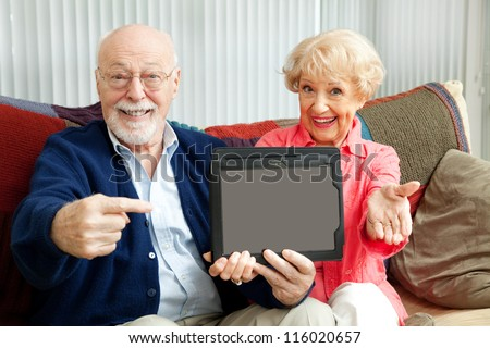 Senior couple pointing to a message on their tablet PC. - stock photo