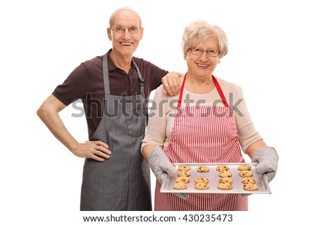 Senior couple posing with homemade chocolate chip cookies isolated on white background - stock photo