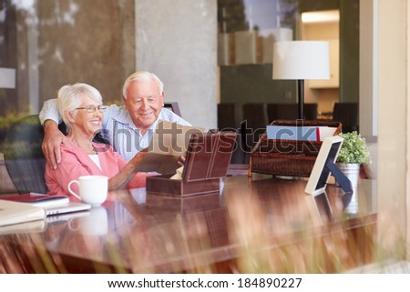 Senior Couple Putting Letter Into Keepsake Box - stock photo