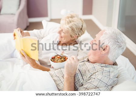 Senior couple reading book while having breakfast on bed at home - stock photo