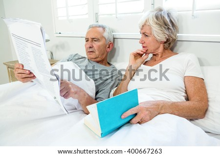 Senior couple reading newspaper on bed at home - stock photo