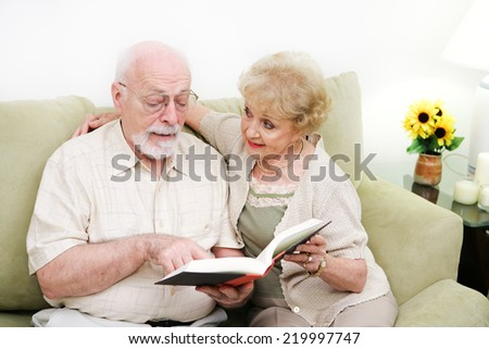 Senior couple relaxing at home and reading a book.   - stock photo