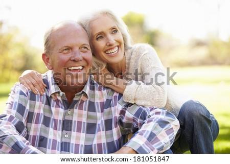 Senior Couple Relaxing In Autumn Landscape - stock photo
