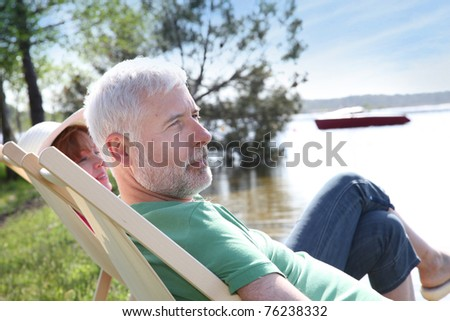 Senior couple resting in deck chair - stock photo