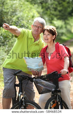 Senior couple riding bicycle and looking at map - stock photo