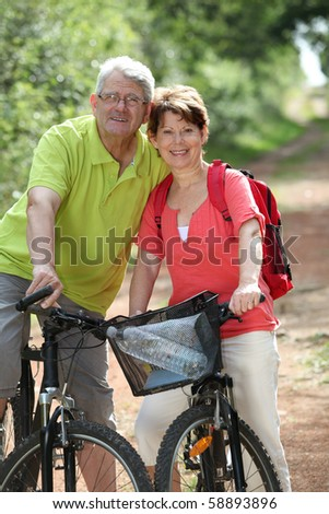 Senior couple riding bicycle in countryside - stock photo