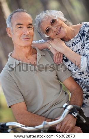 Senior couple riding bikes - stock photo