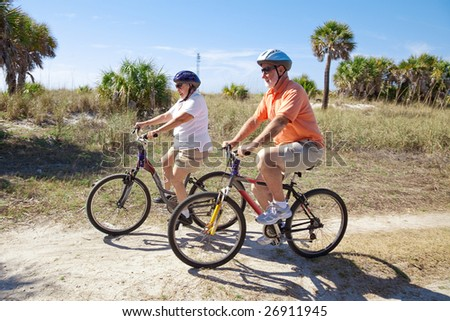 Senior couple riding bikes at the beach, wearing sunglasses and helmets.  Focus on the woman. - stock photo